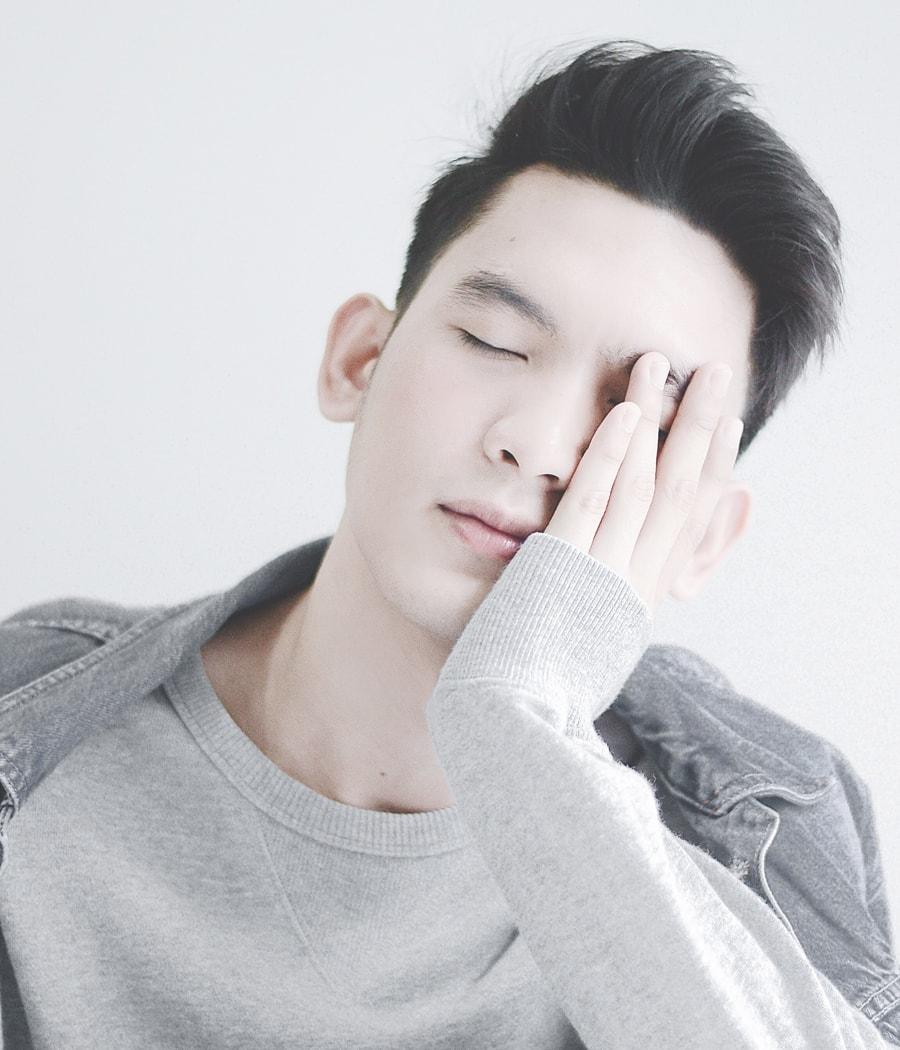 Junge stützt erschöpft den Kopf in die Hand