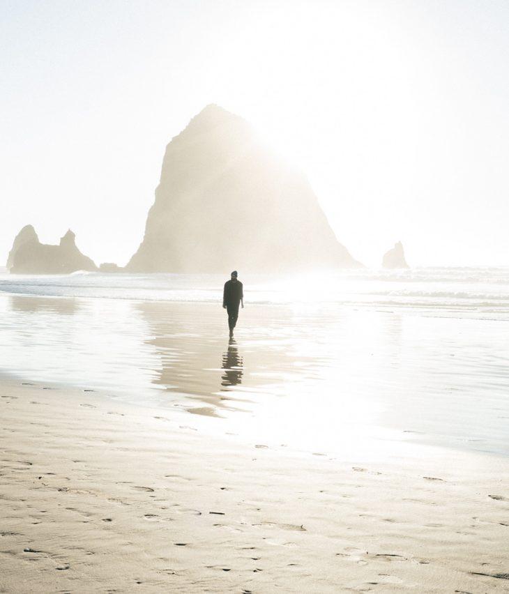Mann geht am Strand im Sonnenuntergang